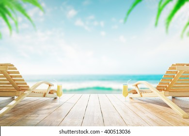 Two chaise longues and cocktails at the beach with clear skies and palm trees