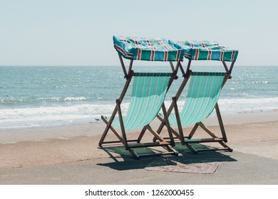Two chaise-longs on the beach