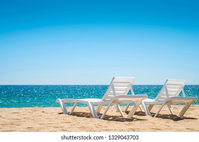 Two chaise-longues on the beach without people