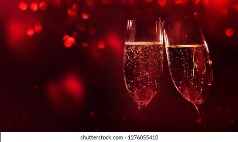 Two champage glasses in front of a valentines background with red hearts