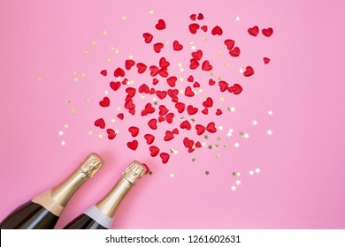 Two champagne bottles with red hearts and golden confetti on pink background. Flat lay of Valentines Day celebration concept