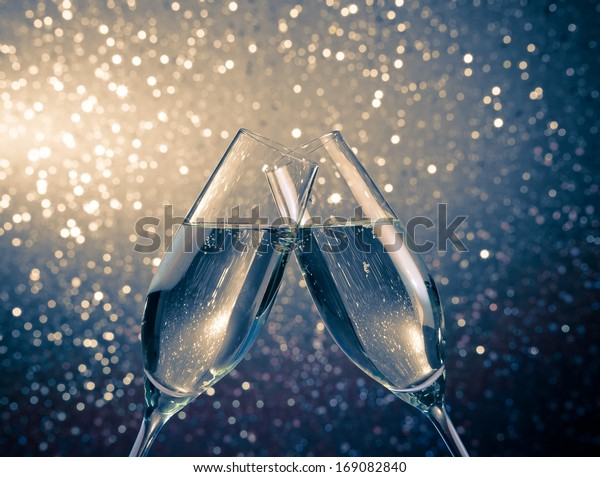 two champagne flutes with golden bubbles make cheers on blue light bokeh background with space for text