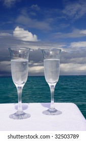 Two Champagne Flutes Set on a Table with the Blue Ocean Surrounding Bermuda in the Background