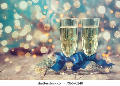 Two champagne glass on christmas bokeh with snow,lights,fir and gift boxes on blue background