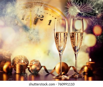 two champagne glasses against holiday lights and fireworks - new year celebration