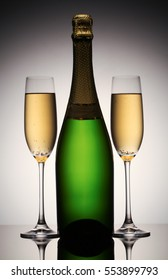 Two champagne glasses and bottle on gradient  background