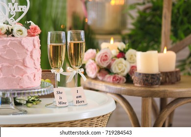Two champagne glasses with cake on table in the room. Concept lesbian wedding