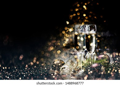 Two champagne glasses and christmas decoration over dark golden bokeh background. New year and christmas luxury party celebration. Sparkling new year 2020 backdrop layout design.