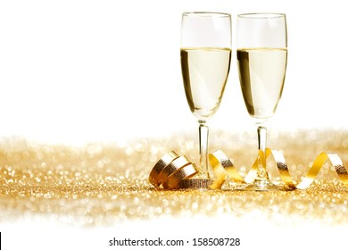 Two champagne glasses and decoration on golden background