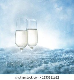 Two champagne glasses in frosty snow with blue bokeh sky