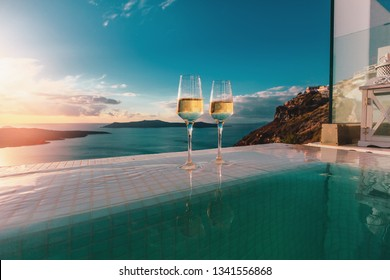 Two champagne glasses on the edge of infinity swimming pool at sunset, Santorini island. Drink, celebrate, vacation and summer concept.