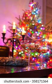 Two champagne glasses on illuminated christmas tree defocused background. Multicolored vibrant vertical image.