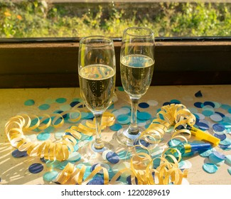 Two champagne glasses on the windowsill with confetti and streamers