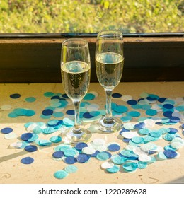 Two champagne glasses with champagne on the windowsill in sunshine with blue confetti