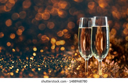 Two champagne glasses over golden bokeh background. New year and christmas luxury party celebration. Sparkling new year 2020 backdrop layout design.