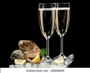 Two champagne glasses with oysters and lemon slices