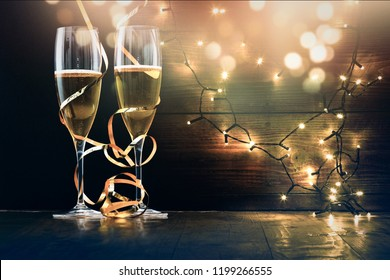 two champagne glasses with ribbons against holiday lights and fireworks - New Year celebrations