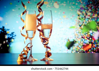 two champagne glasses with ribbons and falling confetti - New Year celebrations