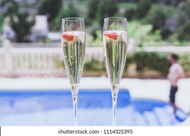 Two champagne glasses with strawberry on sunny terrace outdoor patio overlooking swimming pool at summer day outside of the city.Relaxing holidays concept