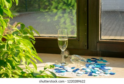 Two champagne glasses in the sunlight on the windowsill with blue confetti