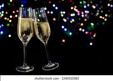 two champagne glasses toast against a dark background with colorful bokeh lights, new year and party concept with copy space