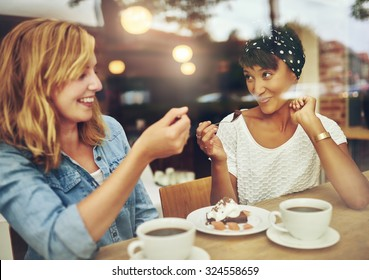 Two charismatic multi ethnic young girl friends sit at a counter in a cafe enjoying a cup of coffee while laughing and chatting
