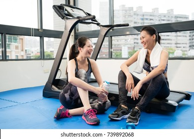 two charming Asian girls take a rest break talking chat after running treadmill and drinking water in the fitness gym.