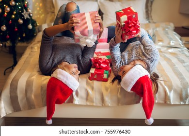 Two charming attractive young girls laying on the bed with heads on the edge while lying on the back with gift boxes looking each other for Christmas holidays with happiness.
