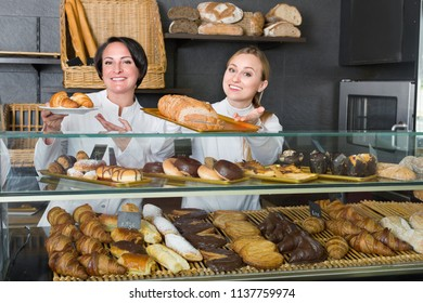 Two charming female cooks demonstrating and selling pastry in the cafe counter