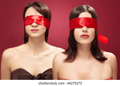Two charming girls blindfold on a red background
