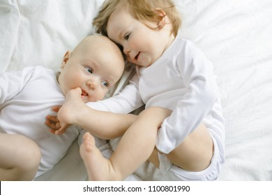 Two charming little babies lie on the white sheet and smile