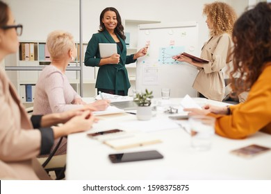 Two charming women making presentation together at businessmeeting in modern office room