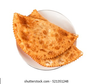 Two Chebureks on white plate isolated with clipping path. Top view. Pasties.