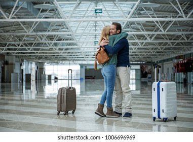 Two cheerful adults hugging each other before departure while standing in the terminal. Suitcases are apart of them