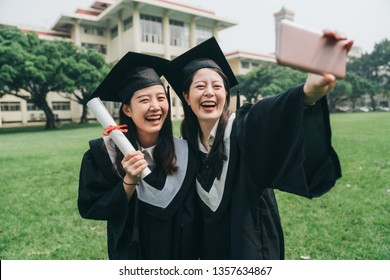 two cheerful asian college girl study abroad standing outdoor on lawn finish bachelor degree. Capturing happy moments. happy female student in graduation gowns making selfie smiling hold smart phone
