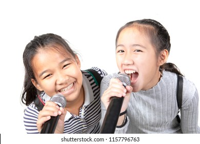 two cheerful asian teenager singing with microphone  isolated white background