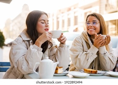 Two cheerful attractive women friends having tea and cakes at the cafe outdoors