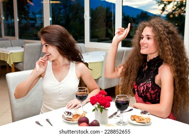 Two cheerful beautiful girls having lunch in the cafe and waving her hand