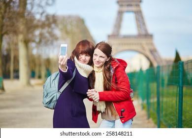 Two cheerful beautiful girls in Paris doing selfie near the Eiffel tower