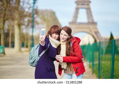 Two cheerful beautiful girls in Paris taking selfie using mobile phone near the Eiffel tower