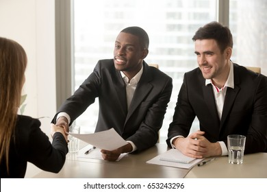 Two cheerful black and white recruiters welcoming female applicant on job interview, african and caucasian hr managers greeting candidate for vacant position, handshaking and good first impression