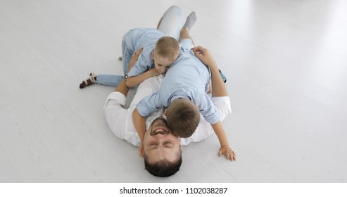 Two cheerful boys run to dad and play with him. A happy father lies on a white floor and hugs his sons.