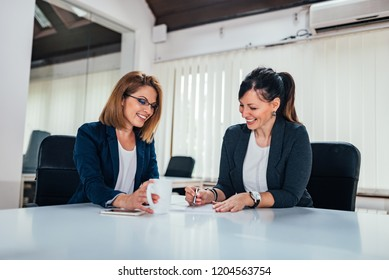 Two cheerful business woman working at conference table.