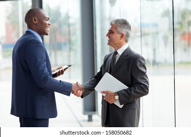 two cheerful businessman handshaking in conference hall