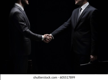 Two cheerful businessman shaking hands and looking at each other