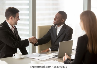 Two cheerful businessmen handshaking at formal meeting, starting finishing negotiations, african entrepreneur wearing black suit white shirt and caucasian partner shake hands, making profitable deal
