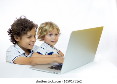Two cheerful children 4 and 9 years old, using a computer sitting at a desk in front of a white background