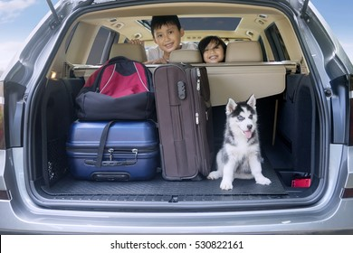 Two cheerful children smiling inside a car with husky dog and luggage for traveling