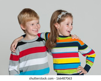 Two cheerful children are standing together on the grey background