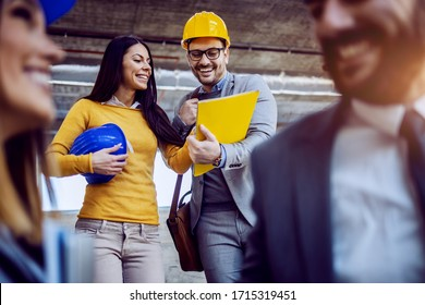 Two cheerful colleagues going down the stairs in building in construction process and looking at folder with files. In foreground are other two colleagues smiling and chatting.